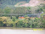 [Panama Canal Railroad alongside canal; major earthworks in the background]